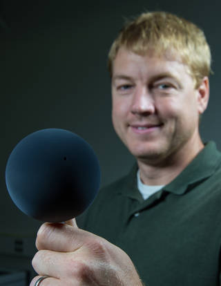 Principal Investigator Phillip Chamberlin holds a sphere coated in super-black carbon nanotubes. Credits: NASA/W. Hrybyk