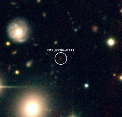 """Figure 1. Color composite-image of IMS J2204+0111 at z=6 (about 1 billion years after the Big Bang). IMS J2204+0111 is the red object at the center and its distance from us is 12.8 billion light years. Because of the expansion of the universe, distant objects like IMS J2204+0111 move away from us almost at the speed of the light, making their light to shift into near-infrared wavelength (phenomenon, called """"redshift""""). This makes them look very red in comparison to other objects, and this special color feature enabled the team to identify distant quasar candidates."""
