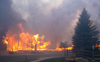 """Photo taken during the 2012 Waldo Canyon wildland urban interface (WUI) fire showing homes in a Colorado Springs, Colo., neighborhood that were ignited as a result of """"structure-to-structure"""" fire spread, a distinguishing characteristic of WUI fires. Image credit: Colorado Springs Fire Department"""