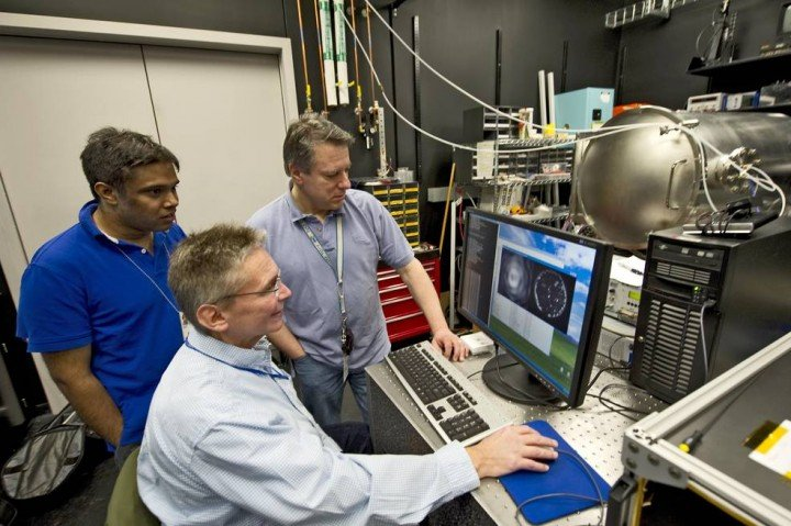 In this image taken in 2012, Rick Lyon (foreground), Udayan Mallik (left), and Sigma Space's Pete Petrone (right) monitored the progress of wavefront control using the early version of the Visible Nulling Coronagraph that at the time was operating inside a vacuum tank. This version of the instrument proved the VNC concept. Credits: NASA/C. Gunn