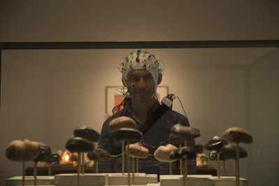 "University of Houston Engineer Jose ""Pepe"" Luis Contreras-Vidal, in collaboration with conceptual artist Dario Robleto, collected electrical brain activity data from more than 400 individuals as they viewed Robleto's exhibit. In this image, Contreras-Vidal views part of the exhibit wearing an EEG cap, which collects the brain activity data. Image credit: UH Cullen College of Engineering"