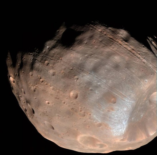 New modeling indicates that the grooves on Mars' moon Phobos could be produced by tidal forces – the mutual gravitational pull of the planet and the moon. Initially, scientists had thought the grooves were created by the massive impact that made Stickney crater (lower right). Credits: NASA/JPL-Caltech/University of Arizona
