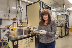 Sandia National Laboratories technologist Catherine Sobczak prepares a silicon wafer to load into a machine. She has been honored with the inaugural Thin Film Distinguished Technologist Award from the American Vacuum Society.