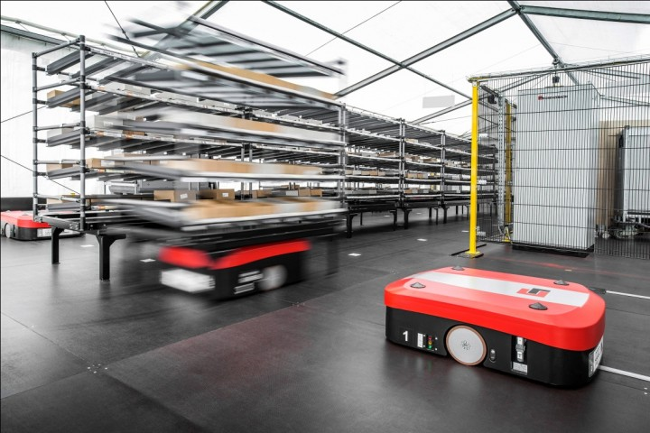 Driverless carries go under the shelves, lift them and transport them autonomously to the central picking station. They also take care of charging themselves and do not drive in the same areas where people work. Image courtesy of audi-mediacenter.com.
