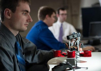 The senior design project for computer engineering students Alex Young (foreground), Zach Mennen (middle), and John Tollefson is to build a robot—including writing the code to make it operational—that sends high-resolution camera images to a head-mounted display, called an Oculus Rift, worn by the surgeon. The robot changes position when the surgeon moves his hand over a Leap Motion sensor—a device similar to a mouse but doesn't require touch—allowing him to see from a different angle without shifting position or touching the robot. Image credit: Justin Torner.