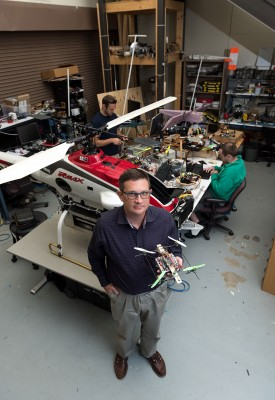 Eric Johnson, associate professor in the School of Aerospace Engineering, holds a 1.1-pound quadrotor designed and built by his students that can replicate the autonomous navigational and sensing performance of the 200-pound commercial helicopter behind him.