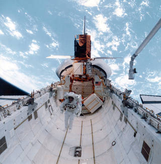 The Solar Maximum Mission spacecraft berthed to the Space Shuttle cargo bay for repairs in April 1984. Credits: NASA