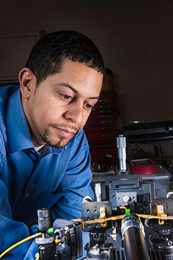 Sandia National Laboratories researcher Charles Reinke studies a tiny phononic/photonic filter nestled among test equipment on a green, stamp-sized substrate toward the picture's bottom-right.