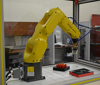 Robot challenged to demonstrate its dexterity on NIST test artifacts. The new ARIAC competition will focus on agility—how well robots can perform a diverse set of tasks and how quickly they can be re-tasked. Image credit: NIST/D. Russell