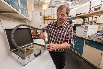 NIST chemist Tom Bruno, who invented a method for recovering trace chemicals such as environmental pollutants and forensic evidence, uses a portable version of the instrument to sample vapor inside an old paint can. The underlying technique is called PLOT-cryoadsorption, or PLOT-cryo - short for porous layer open tubular cryogenic adsorption. Image credit: Dave Neligh