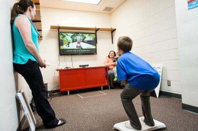 Xavier Hansen stands on a Wii Connect balance board and practices a Wii ski jump pose while mirroring his body position to match that of a video-game shape displayed on a computer monitor. Sitting in the background at right is Xavier's mother, Gail Hansen. Image credit: Jeff Miller