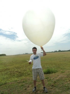 Angel Adames at the DYNAMO field campaign in the Maldive Islands in February 2012. He is holding a research weather balloon and a box that will track temperature, dew point, etc., at different heights. Image credit: University of Washington