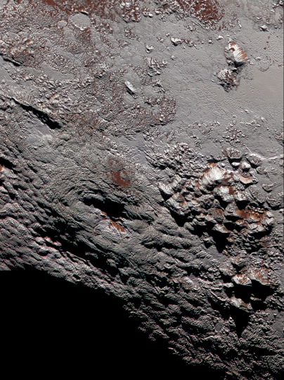 Wright Mons in Color. This composite image of a possible ice volcano on Pluto includes pictures taken by the New Horizons spacecraft's Long Range Reconnaissance Imager (LORRI) on July 14, 2015, from a range of about 30,000 miles (48,000 kilometers), showing features as small as 1,500 feet (450 meters) across. Sprinkled across the LORRI mosaic is enhanced color data from the Ralph/Multispectral Visible Imaging Camera (MVIC), from a range of 21,000 miles (34,000 kilometers) and at a resolution of about 2,100 feet (650 meters) per pixel. The entire scene is 140 miles (230 kilometers) across. Credits: NASA/JHUAPL/SwRI