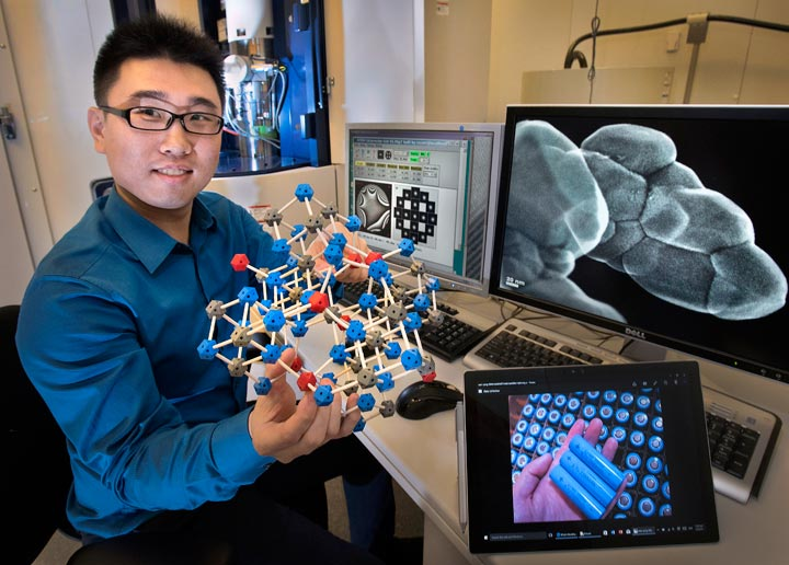 Brookhaven Lab physicist Huolin Xin in front of an aberration-corrected scanning transmission electron microscope at the Center for Functional Nanomaterials