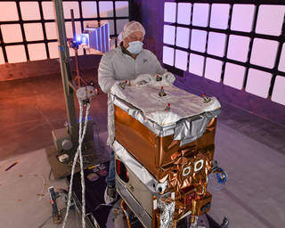 A Ball Aerospace engineer adjusts the thermal insulation on NASA's Green Propellant Infusion Mission spacecraft bus following integration of the propulsion system. Credits: Ball Aerospace