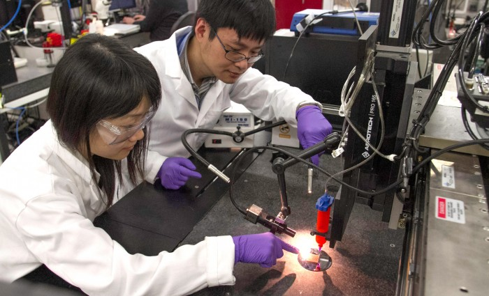 LLNL material and biomedical scientist Fang Qian (left) and engineer Cheng Zhu demonstrate a direct ink writing 3D printer they used to manufacture supercapacitors out of a graphene-based aerogel. Photos by Julie Russell/LLNL