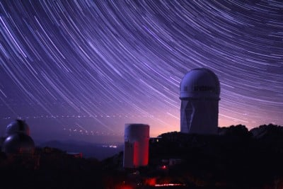 Star trails take shape around Kitt Peak National Observatory in this long-exposure image. The 4-meter Mayall telescope building, at right, now houses Mosaic-3, a new infrared camera built by a collaboration that includes Berkeley Lab scientists. Image  credit: P. Marenfeld and NOAO/AURA/NSF