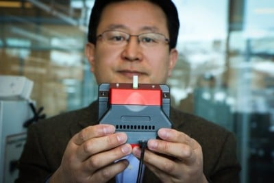 University of Utah materials science and engineering professor Ling Zang holds up a prototype handheld detector his company is producing that can sense explosive materials and toxic gases. His research team developed a new material for the detector that can sense alkane fuel, a key ingredient in such combustibles as gasoline, airplane fuel and homemade bombs. Image credit: Dan Hixson/University of Utah College of Engineering