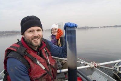 Jonathan Woodruff and Christine Brandon collect core samples of sediment