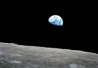 Contrasted against the stark, crater-marked lunar surface, the Earth is seen rising above the moon on Dec. 24, 1968. As Apollo 8 orbited the moon, Earth is 240,000 miles away. Credits: NASA/Bill Anders