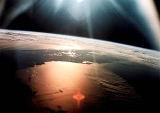 The morning sun reflects on the Gulf of Mexico and the Atlantic Ocean as seen from the Apollo 7 spacecraft on Oct. 20, 1968. Most of the Florida peninsula appears as a dark silhouette at an altitude of 120 miles above Earth. Credits: NASA