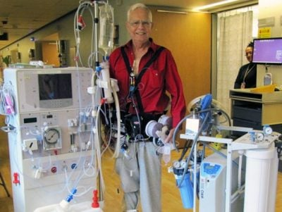Chuck Lee, one of the patients in the early clinical testing of the Wearable Artificial Kidney, sports the experimental device while standing next to a standard kidney dialysis machine. Image credit: Sandy Lee