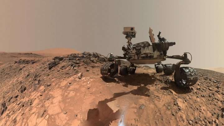 """This low-angle self-portrait of NASA's Curiosity Mars rover shows the vehicle at the site from which it reached down to drill into a rock target called """"Buckskin."""" Bright powder from that July 30, 2015, drilling is visible in the foreground. Credit: NASA/JPL-Caltech/MSSS"""