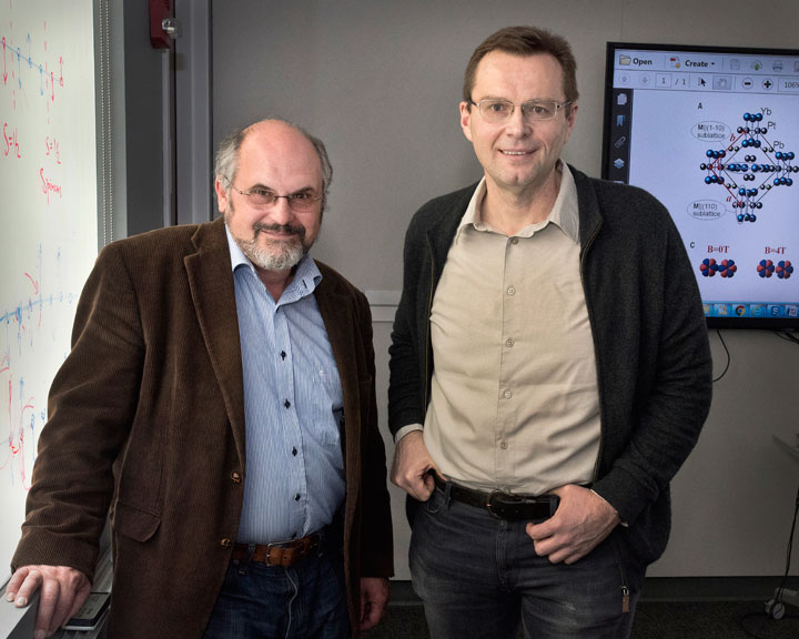 Brookhaven Lab theoretical physicist Alexei Tsvelik (left) and physicist Igor Zaliznyak, with the crystal structure of the studied metallic compound shown on the screen in the background.
