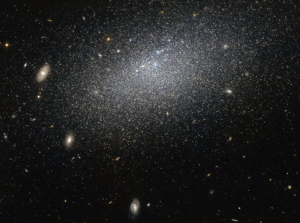 The drizzle of stars scattered across this image forms a galaxy known as UGC 4879. UGC 4879 is an irregular dwarf galaxy — as the name suggests, galaxies of this type are a little smaller and messier than their cosmic cousins, lacking the majestic swirl of aspiral or the coherence of anelliptical. This galaxy is also very isolated. There are about 2.3 million light years between UGC 4879 and its closest neighbour, Leo A, which is about the same distance as that between the Andromeda Galaxy and the Milky Way. This galaxy's isolation means that it has not interacted with any surrounding galaxies, making it an ideal laboratory for studying star formation uncomplicated by interactions with other galaxies. Studies of UGC 4879 have revealed a significant amount of star formation in the first 4-billion-years after the Big Bang, followed by a strange nine-billion-year lull in star formation, ended 1-billion-years ago by a more recent reignition. The reason for this behaviour, however, remains mysterious, and the solitary galaxy continues to provide ample study material for astronomers looking to understand the complex mysteries of starbirth throughout the Universe.