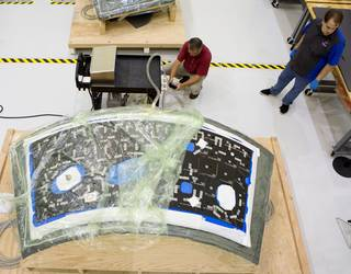 In the Neil Armstrong Operations and Checkout Building at NASA's Kennedy Space Center, technicians have begun bonding thermal protection system tiles to the nine panels the will cover the Orion crew module for the agency's first unpiloted flight test with the Space Launch System (SLS) on the agency's Journey to Mars. Credits: NASA/Cory Huston