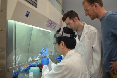 Assistant Professor Iwijn De Vlaminck, right, and graduate student Philip Burnham, center, look on as Min Seong Kim '18 works at the biosafety cabinet. Credit: Sarah Nickerson/Biomedical Engineering