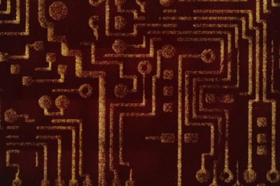 Researchers at MIT and the University of California at San Diego have delivered artificial genetic circuits into bacteria, allowing the microbes to kill cancer cells in three different ways. Here, an image of a motherboard has been micropatterned using programmable probiotic bacteria. The bright lines are composed of dots made of bacteria. This technique was developed in the lab of MIT professor Sangeeta Bhatia, who is a senior author on the new paper. Credit: Vik Muniz and Tal Danino