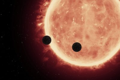 An artist's depiction of planets transiting a red dwarf star in the TRAPPIST-1 System. Image courtesy of NASA/ESA/STScl