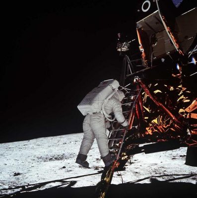 "Astronaut Edwin E. Aldrin Jr., lunar module pilot, descends the steps of the Lunar Module (LM) ladder as he prepares to walk on the moon. He had just egressed the LM. This photograph was taken by astronaut Neil A. Armstrong, commander, with a 70mm lunar surface camera during the Apollo 11 extravehicular activity (EVA). While Armstrong and Aldrin descended in the LM ""Eagle"" to explore the moon, astronaut Michael Collins, command module pilot, remained with the Command and Service Modules (CSM) in lunar orbit."