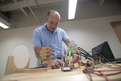 Akbar Sayeed adjusts a one-of-its kind multi-beam MIMO antenna, capable of sending out and steering several millimeter-wave signal beams simultaneously in order to connect end users to a 5G network. Image credit: Stephanie Precourt