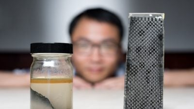 Kai Yu, a former postdoctoral researcher in The George W. Woodruff School of Mechanical Engineering at Georgia Tec, sits behind a piece of carbon fiber composite immersed in alcohol. Image credit: Rob Felt, Georgia Tech
