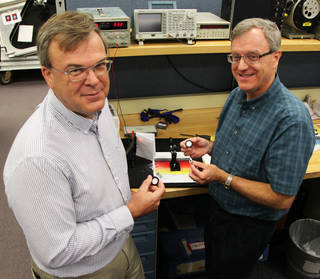 Co-principal investigators Mark Nurge, Ph.D., left, and Robert Youngquist, Ph.D., hold sample disks with prototype cryogenic selective surface coatings. This innovative technology could enable storing super-cold, or cryogenic, liquids and support systems that shield astronauts against radiation during the Journey to Mars. Credits: NASA/Bill White