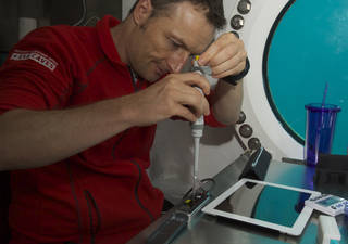 NASA Extreme Environment Mission Operations (NEEMO) crew member, Matthias Maurer of ESA, works on inserting samples into the MinION DNA sequencer as part of the Biomolecule Sequencer experiment. Researchers tested the device aboard the analog to minimize unknowns and see how the device worked in various extreme environments. Credits: NASA