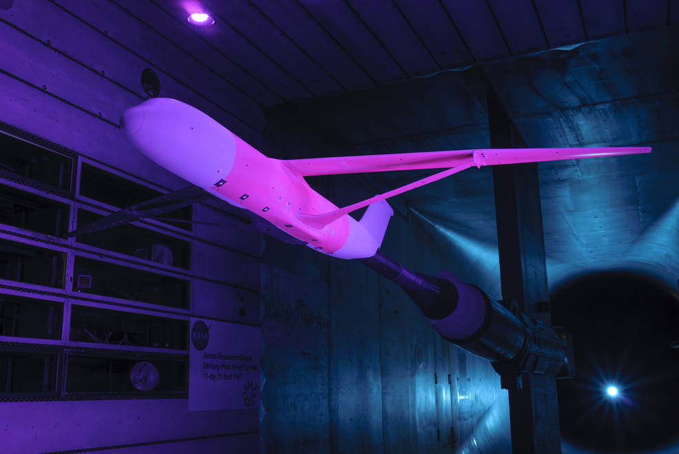 An aircraft design that could reduce fuel use, emissions and noise is set up for a test in a wind tunnel at NASA's Ames Research Center in California in which pink-colored pressure-sensitive paint is applied to the vehicle. The pink paint shines when exposed to blue light, glowing brighter or dimmer depending on air pressure in the area.