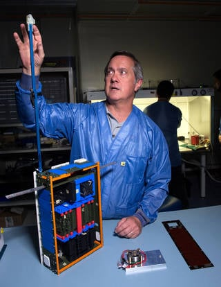 Dellingr Project Manager Chuck Clagett points to the CubeSat's boom, at the end of which is a magnetometer, an instrument that takes measurements of its magnetic surroundings. Dellingr also carries two no-boom magnetometers, a first for such miniature satellites. Credits: NASA's Goddard Space Flight Center/Bill Hrybyk