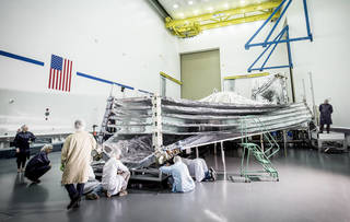 NASA's Webb telescope sunshield, opened for inspection. In this photo, engineers and scientists examine the sunshield layers on this full-sized test unit. Credits: Northrop Grumman Corporation/Alex Evers