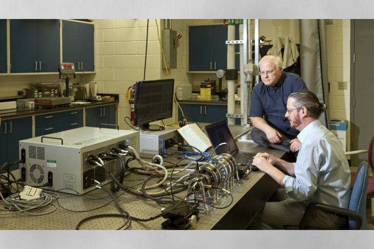 L-R: Roger Kisner, Alexander Melin with the magnetic suspension testbed and its associated electronics and controls.