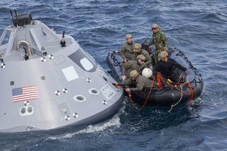 U.S. Navy divers and other personnel in a small Zodiac boat secure a tether line to an attach point on a test version of the Orion crew module Oct. 31 during Underway Recovery Test 5 in the Pacific Ocean off the coast of California. Photo credit: NASA/Bill White