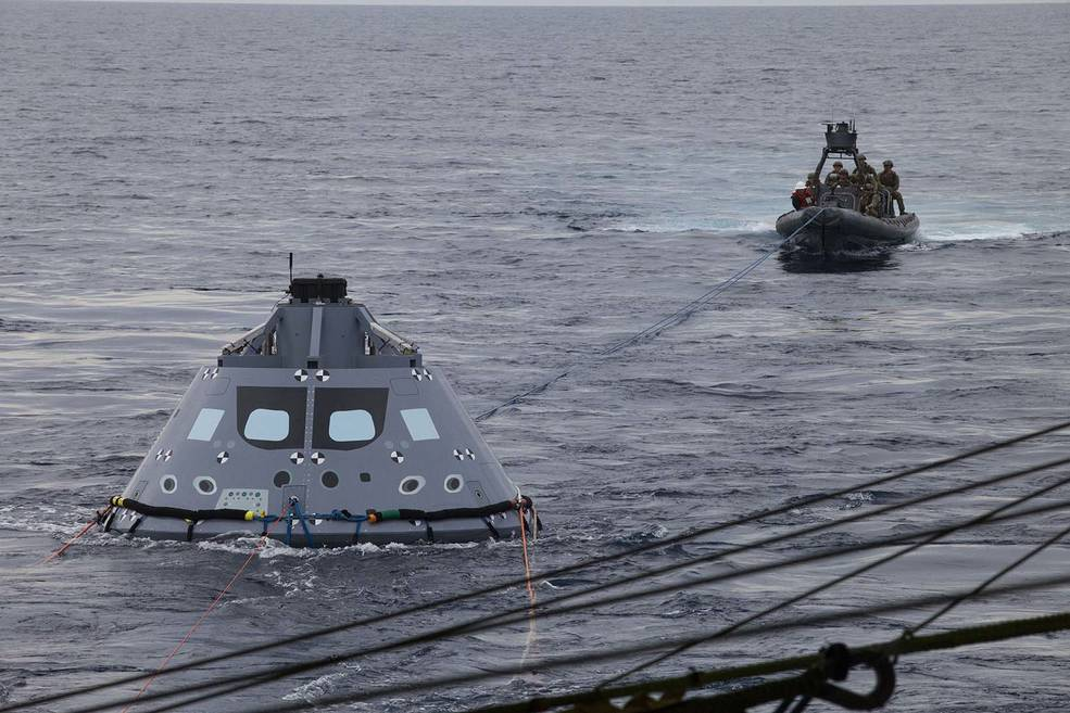 U.S. Navy divers and other personnel in a rigid hull Zodiac boat attached tether lines to a test version of the Orion crew module Oct. 27 during Underway Recovery Test 5 in the Pacific Ocean off the coast of California. NASA's Ground Systems Development and Operations Program and the U.S. Navy are conducting a series of tests using the USS San Diego, various watercraft and equipment to practice for recovery of Orion on its return from deep space missions. Photo credit: NASA/Bill White