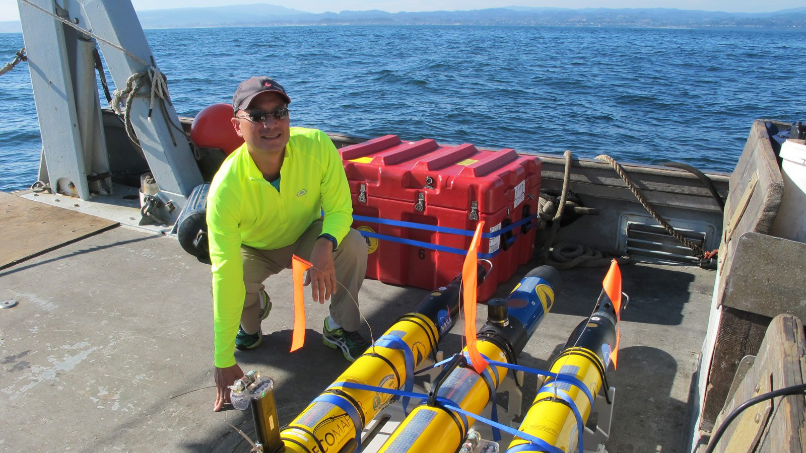 JPL's Steve Chien with several of the underwater drones used in a research project earlier this year. Chien, along with his research collaborators, are developing artificial intelligence for these drones. Image Credit: NASA/JPL-Caltech.