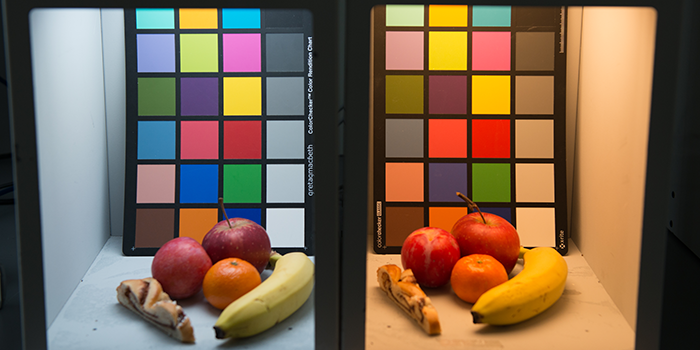 Experimental setup with fruit (and cake) and a colour checker chart shows how differently two light sources render the colours, even though the light from each has the same value on the Ra index. Both light sources have a Ra value of 95. In the box on the left, the light source is a cold white light with a colour temperature of 5,747 kelvin, while the light source in the right-hand box is a warm white light with a colour temperature of approx. 2,631 kelvin.