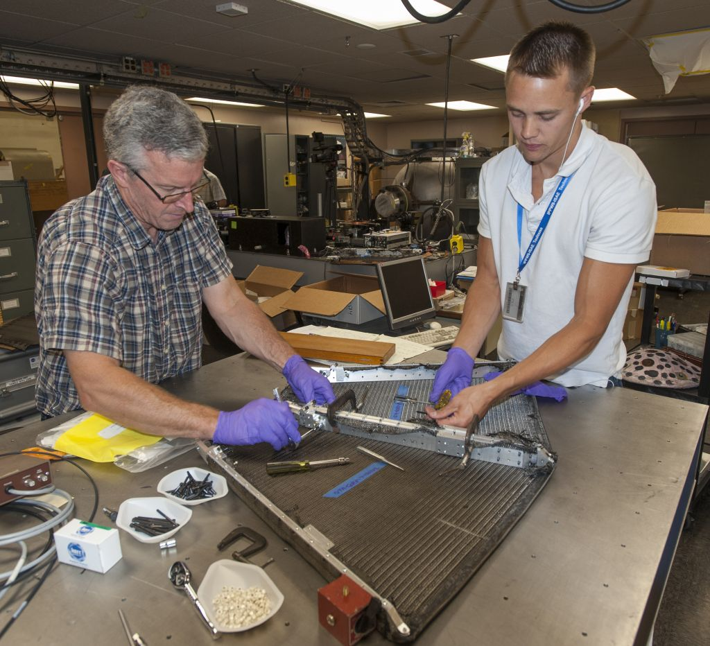 Paul Wercinski, ADEPT project manager and Cole Kazemba, ADEPT system engineer, attach the woven carbon fabric skin to the ribs of an early version of ADEPT in the assembly lab at Ames. Image credits: NASA Ames Research Center/ Eric James