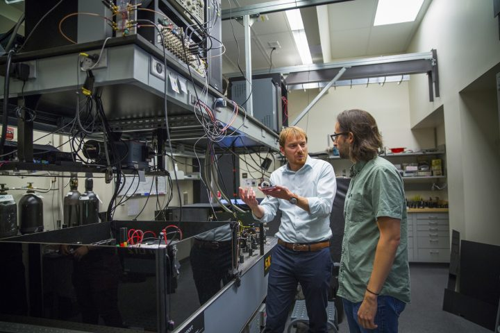 Bassett and David Hopper, a fifth year PhD candidate in Quantum Information Science, discuss the large-scale system that currently makes these quantum processes possible. They plan to reduce this entire system to a single chip.