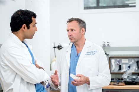 Shane Burch (right), MD, a spinal surgeon in the Deptartment of Orthopaedic Surgery, and Musa Zaid, MD, a research resident in Orthopaedic Surgery, discuss a use of a 3-D printed spine created from a clinical CT scan of a patient with a spinal deformity. Photo by Barbara Ries / UCSF
