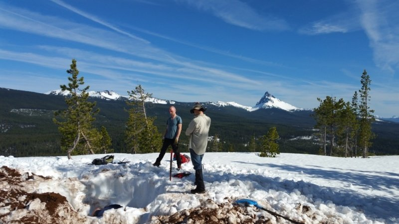 UO graduate students Miles Bodmer (in hole), Brandon VanderBeek, and Gillean Arnoux servicing ShakeAlert site DFAZ in the high Cascades; Mt. Thielsen in background.